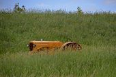 foto of prairie  - A lone  old yellow tractor is barely visible in the long prairie grass - JPG