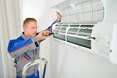 image of air conditioner  - Portrait Of Male Electrician Repairing Air Conditioner Standing On Stepladder - JPG
