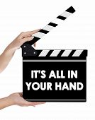 Hands Holding A Clapper Board With It's All In Your Hand Text
