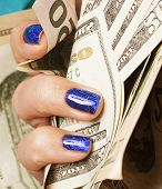 picture of indigo  - close up fingers with blue creative pattern manicure holding dollars - JPG
