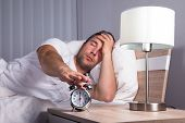 pic of irritated  - Man Irritated With Noise Snoozing Alarm Clock - JPG