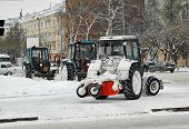 Tractors with snowplowing equipment on streets