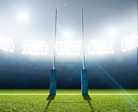 stock photo of illuminated  - A rugby stadium with rugby posts on a marked green grass pitch at night under illuminated floodlights - JPG