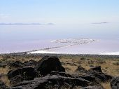 picture of masterpiece  - Spiral Jetty swirls in the pink blue water on a clear day seen from the rocky shore Robert Smithson - JPG