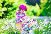 image of little young child children girl toddler  - Happy child riding a bike - JPG
