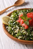 stock photo of tabouleh  - Dietary eastern Tabbouleh salad closeup in a wooden bowl. vertical ** Note: Shallow depth of field - JPG