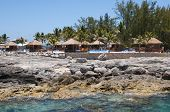 picture of beach hut  - Thatched beach huts on a coral reef in the Carribean with blue sparkling water in the foreground - JPG