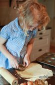 stock photo of pastry chef  - Young girl who is cutting out pastry with pastry cutter - JPG