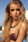picture of beside  - fashion outdoor photo of beautiful sexy tanned girl with long blond hair in elegant bikini posing beside a swimming pool - JPG