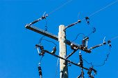 picture of utility pole  - Old wooden telephone or electrical pole and metal bar with cables and insulators on right side against clear blue sky - JPG