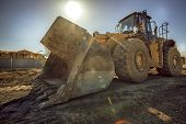 picture of excavator  - Heavy duty construction digger excavator equipment with sun flare - JPG