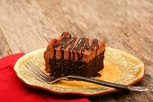 foto of chocolate fudge  - Chocolate sheet cake covered with chocolate icing and chocolate syrup on a plate with a fork - JPG