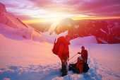 picture of mountain-climber  - climbers at the top of a pass with backpacks meeting the sunrise in the mountains - JPG