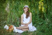 stock photo of milkmaid  - young Woman Has Picnic In Summer Park  - JPG