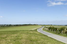 stock photo of long winding road  - A long an winding road on a field with Mont St Michel France in the background - JPG