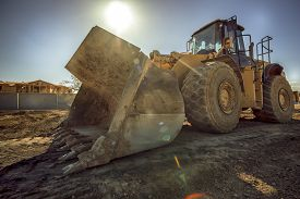 stock photo of power-shovel  - Heavy duty construction digger excavator equipment with sun flare - JPG