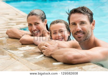 Pretty little girl with her parents in swimming pool. Happy family smiling and looking at camera in