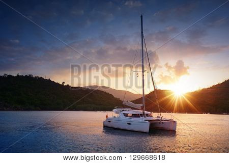 Yacht - Catamaran in the tropical sea at sunset. Yachting theme. Yachting background. Sailing time.