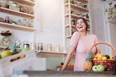 Постер, плакат: Smiling Woman Standing At A Juice Bar Counter