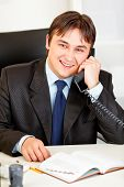 Smiling businessman sitting at office desk and talking on phone