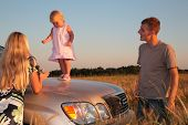 Parents and child on car cowl on wheaten field