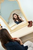 pic of cheval  - Young woman is making her hairstyle in front of mirror - JPG