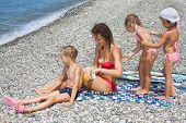 young woman and three children smear each other backs with cream for sunburn on stony beach