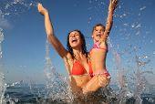 schöne junge Mutter hält ihre kleine Tochter. Sie Baden im Meer. Sprühen. viele Tropfen