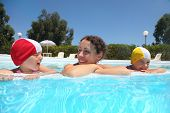 Mother and two girls lie near skirting in  pool and smile
