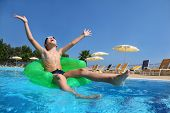 Boy sits on an inflatable arm-chair in  pool and with gladness lifts hands and head upwards in sky,