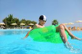 Boy sits on an inflatable arm-chair in  pool under open-skies and floats