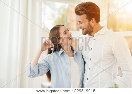 poster of Young Couple Posing For A Photo In A Bright Room. Newlyweds In The New Apartment. The Girl Holds The