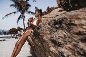 Serious Young Hottie Black Female Is Drinking Fresh Coco Water While Leaning On The Cliff With Beach poster