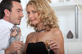 Flirtatious couple drinking champagne at home