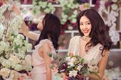 Beautiful Asian Florist Girls Making Bouquet Of Flowers For Sale Against Floral Bokeh Background In  poster