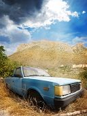 old broken car and mountains