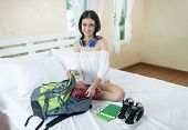 Cheerful Female Packing Suitcase And Getting Ready For Traveling.bedroom Full Of Things Ready To Be  poster
