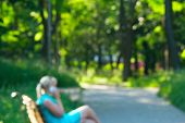 Young Girl Sitting On Bench In City Park And Talking On Phone. Background Is Blurred. Lifestyle Conc poster