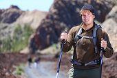 Adventure hiking man. Portrait in mountain landscape. Caucasian male hiker smiling in nature standin