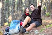 Young happy couple hiking in forest. Smiling couple resting enjoying a break during hike vacations.