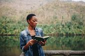 African American woman alone in nature reading a book leisure concept poster
