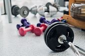 Set Of Equipment For Weightlifting And Fitness: Dumbbells, Barbell And Rowing Machine At Gym. poster
