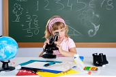 children little girl at school classroom with microscope in science class