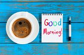 Good Morning - Is Written On Small Notepad With A Cup Of Morning Coffee On Rustic Wood Background Wi poster