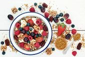 Healthy breakfast super food cereal concept with fresh fruit, granola, yoghurt, nuts and pollen grai poster