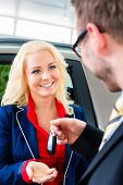 Happy woman with key to new auto in car dealership poster