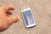 Person Picking Broken Smart Phone (cracked Screen) Of The Cement Floor poster