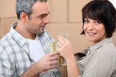Couple drinking champagne in front of a pile of cardboard boxes