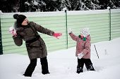 Young Mother And Daughter Have Fun In The Snow