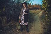 Autumn mood. Beautiful young woman  in autumn clothes posing outdoor.  Seasonal autumn fashion. poster